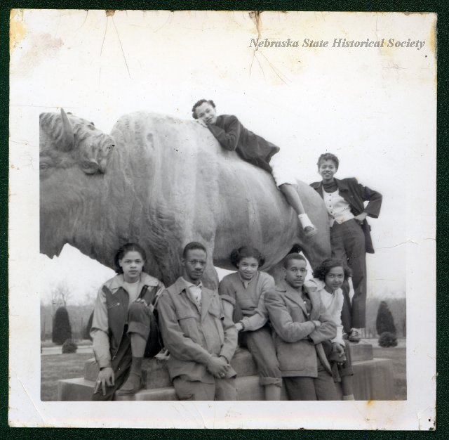 Teenagers are playing on the Pioneers Park buffalo. Joyce Williams is atop the buffalo. circa 1945