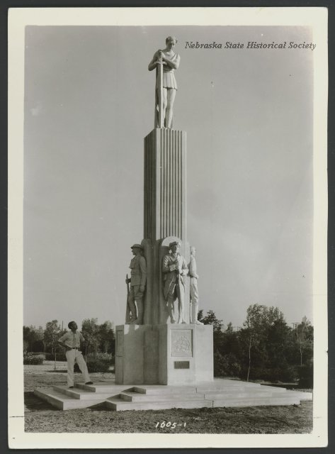 This is the War Memorial designed by Ellis Luis Burman. It stands 150 yards west of the Antelope Dance Pavilion in Antelope Park in Lincoln, Nebraska. The monument represents the spirit of war and victory and is cast marble. At the base of the main shaft stand figures representing the Revolutionary War, Civil War, Spanish-American War and World War I. A man is seen standing at the base looking at the monument. 1937
